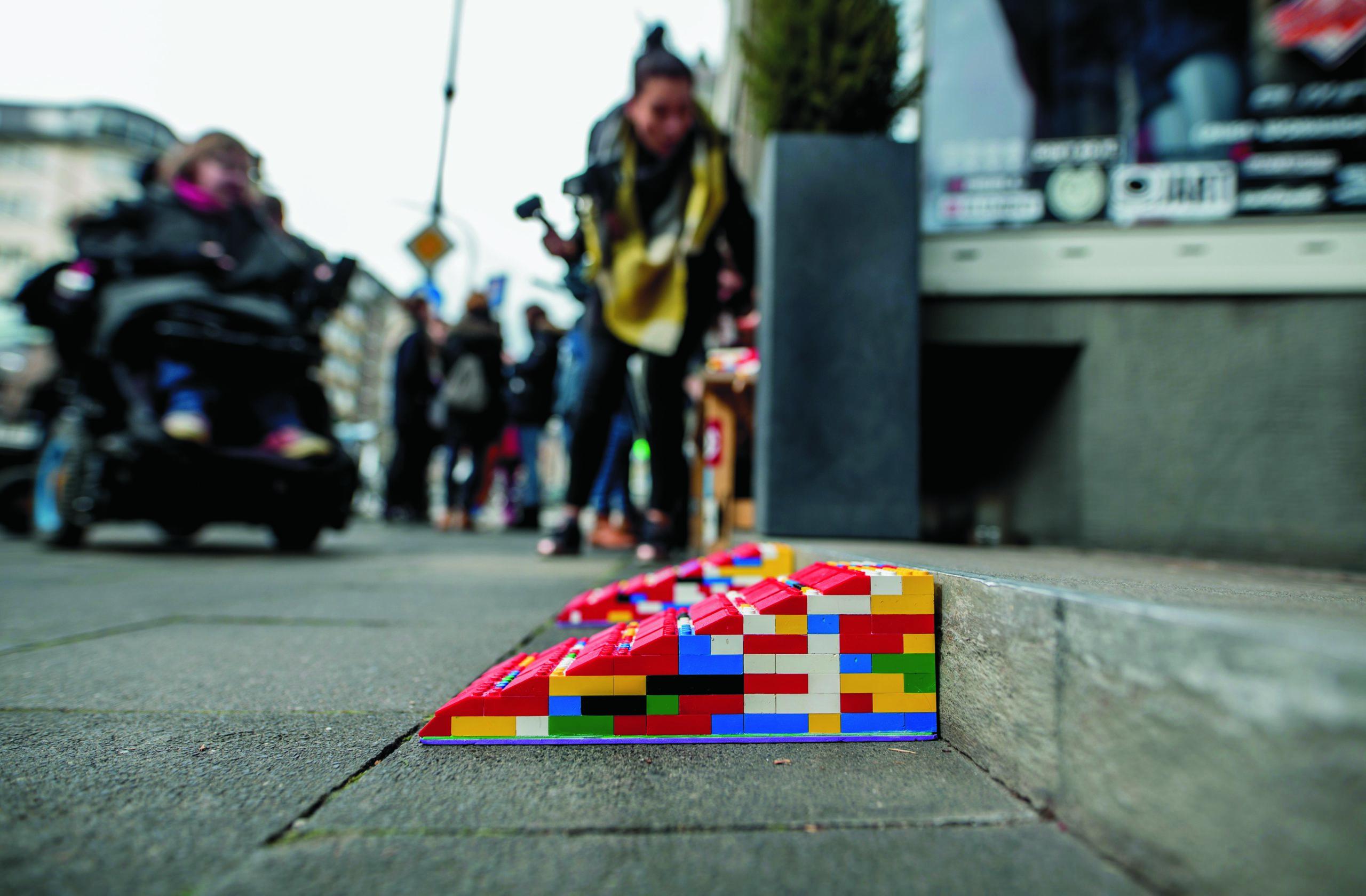 Zwei bunte Rampen aus Lego stehen gegen den Bordstein auf dem Fußgängerweg. Im Hintergrund sieht man verschwommen Menschen.