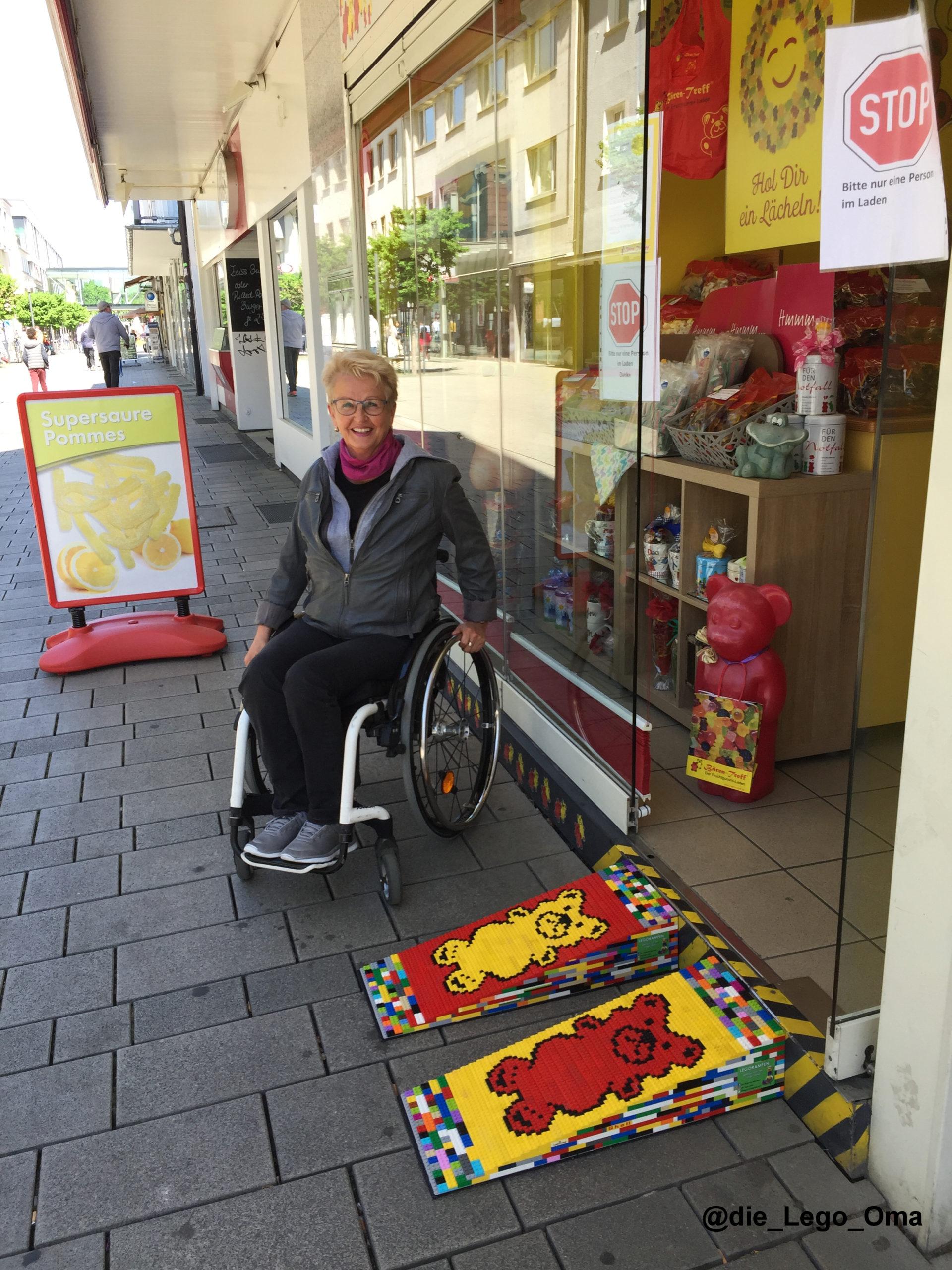 Eine ältere Frau sitzt im Rollstuhl vor einem Gummibärchen-Laden. Daneben sieht man den Eingang. Vor dem Eingang stehen zwei Legorampen im Design des Ladens.