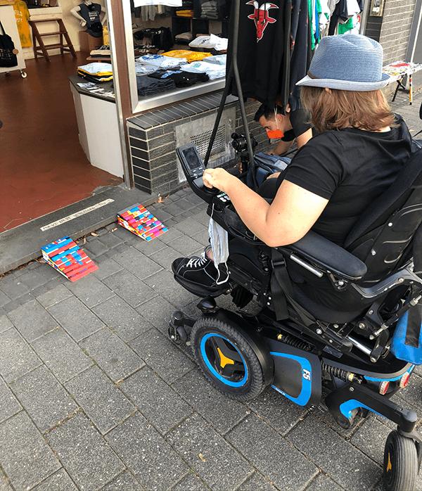 Eine Frau sitzt in einem E-Rolli. Sie steht damit vor den Legorampen eines Geschäftes. Vor dem Geschäft steht eine Kleiderstange mit T-Shirts.