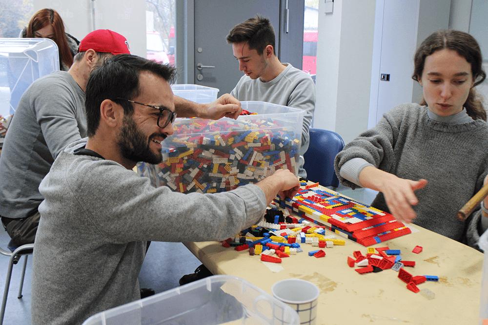 Eine Gruppe Menschen am Tisch, darunter einer im Rollstuhl, bauen an einer Legorampe